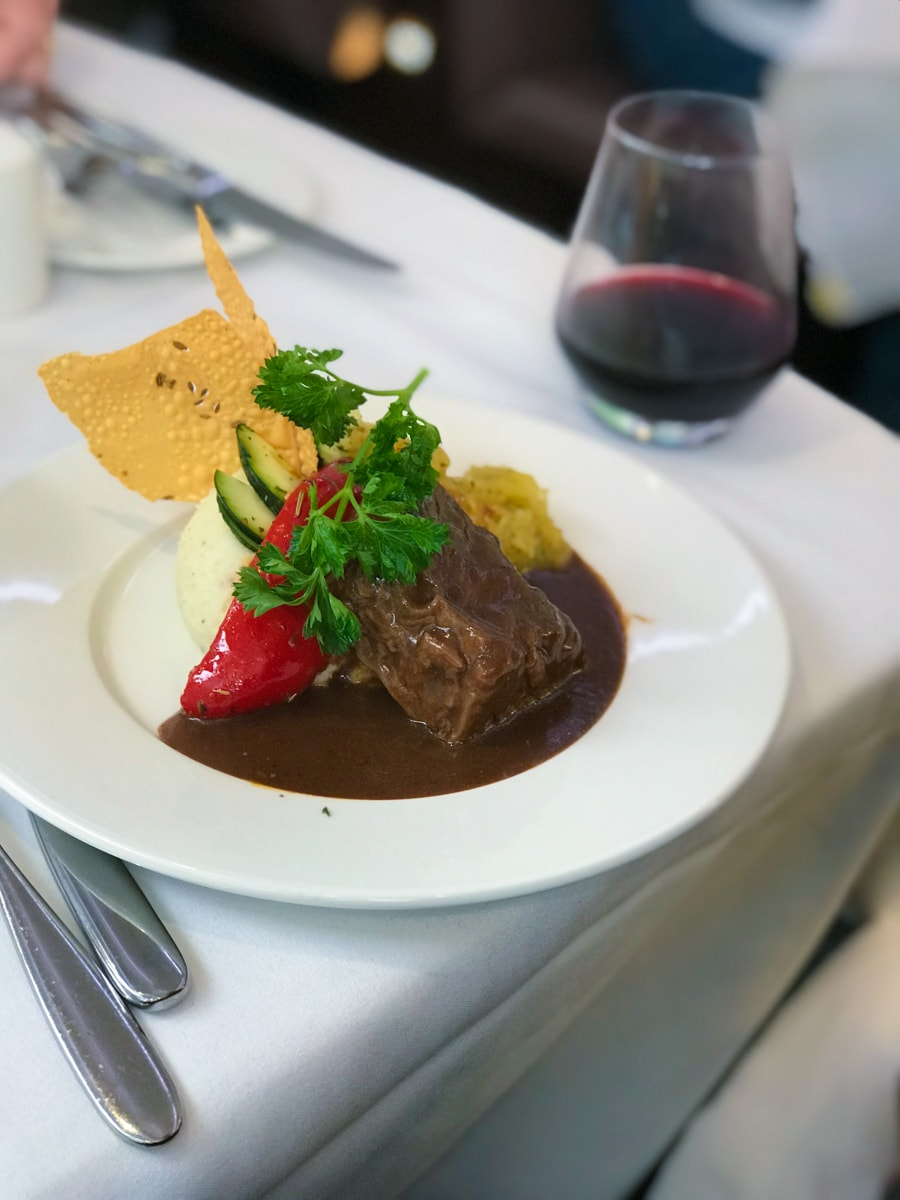 Short ribs and pepper with mashed potatoes and parmesan cheese crisp on white plate with glass of wine.