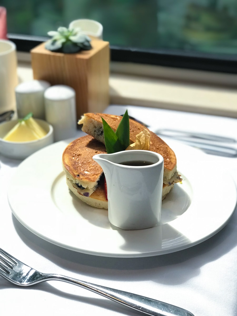 Pancakes with cup of syrup on white plate in front of window.