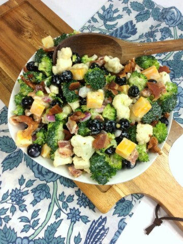 broccoli salad with cheese cubes in a white bowl on a cutting board