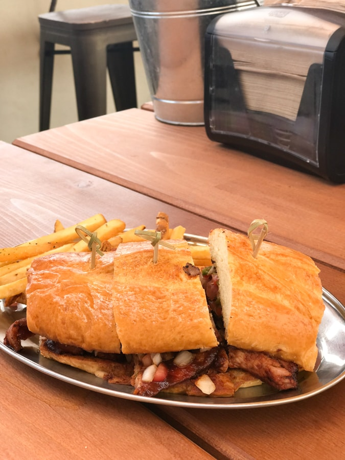 Sandwich with french fries on picnic table.