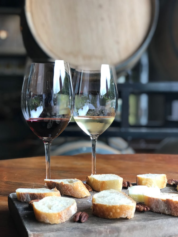 Glass of white wine with a glass of red wine and bread with butter and nuts on wood block.