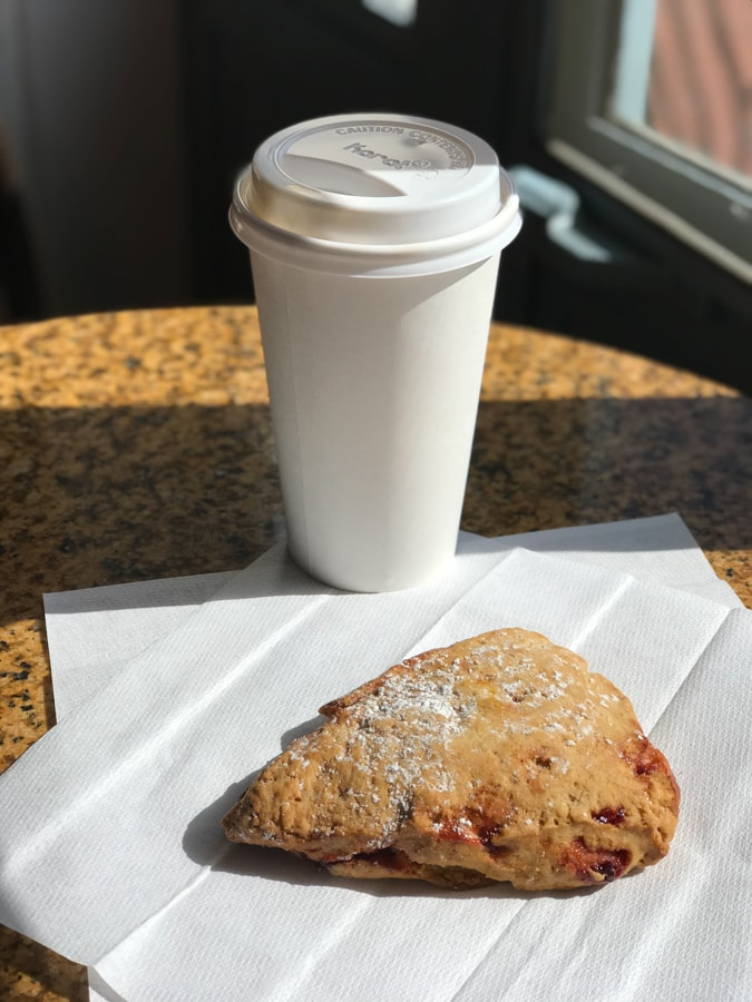 Coffee in a white to-go cup with a scone on a napkin.