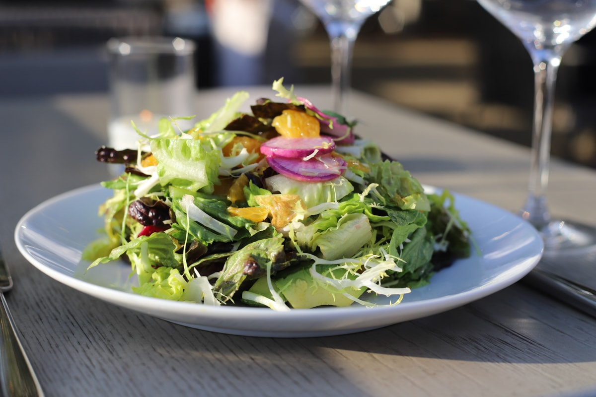 Salad on a white plate on a gray wood table with water glasses.