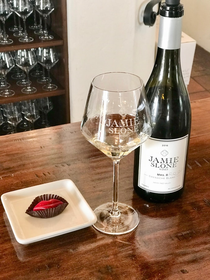 Bottle of wine with white wine in glass and candy on plate on bar.