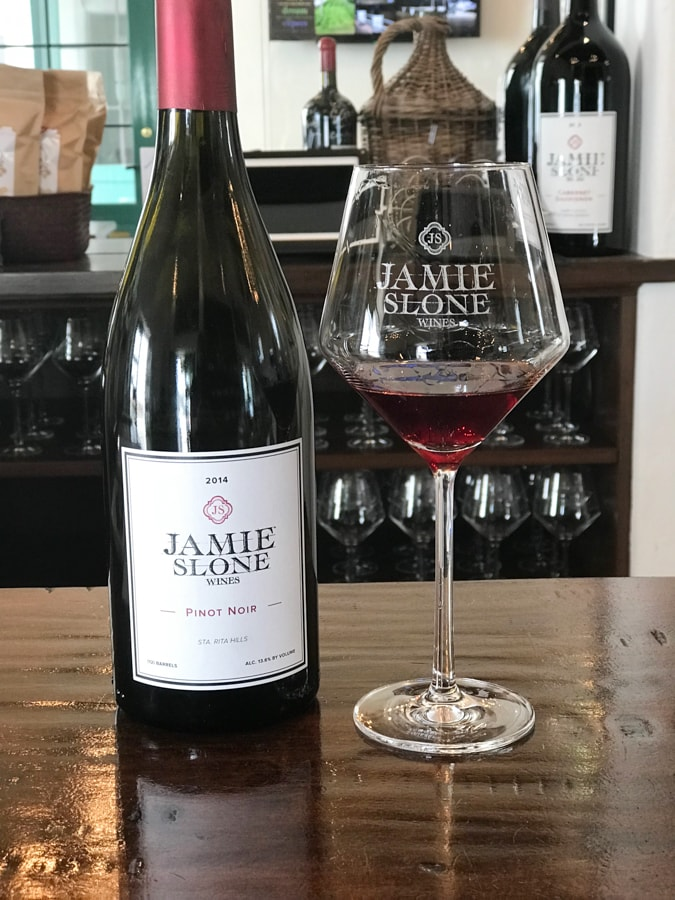 Bottle of wine and a wine glass with red wine on a bar.