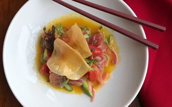 raw tuna and veggies in sauce in white bowl with chopsticks on red material