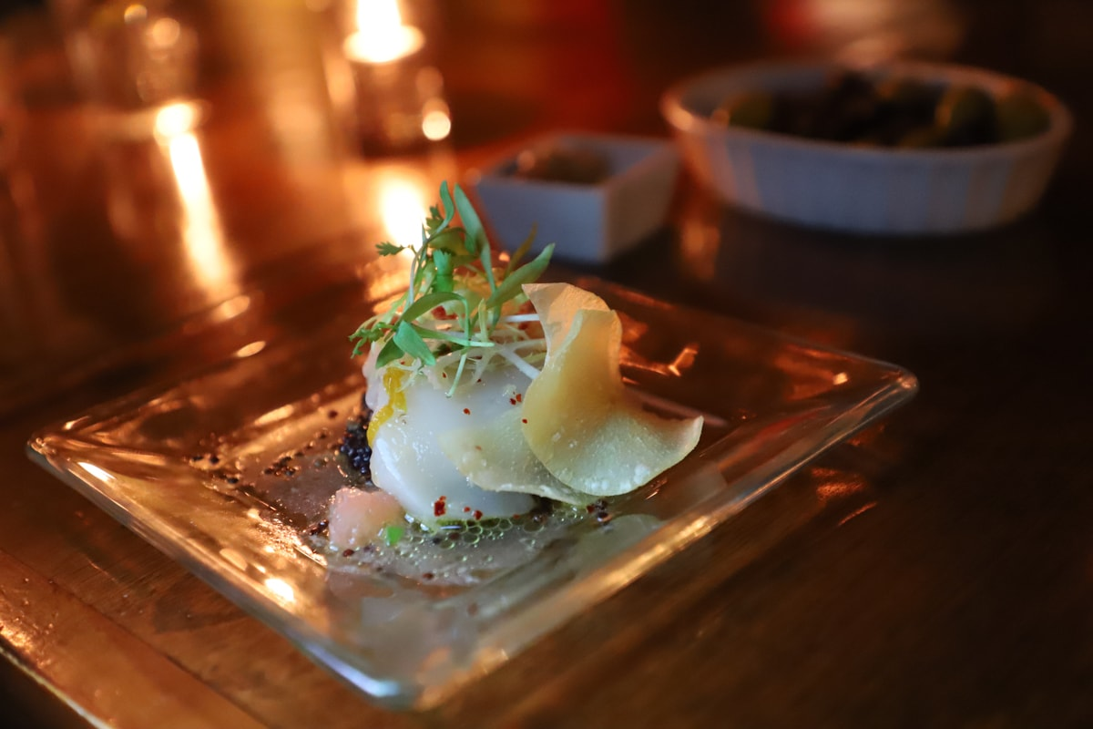 Scallop on plate with potato chip and candle in background.