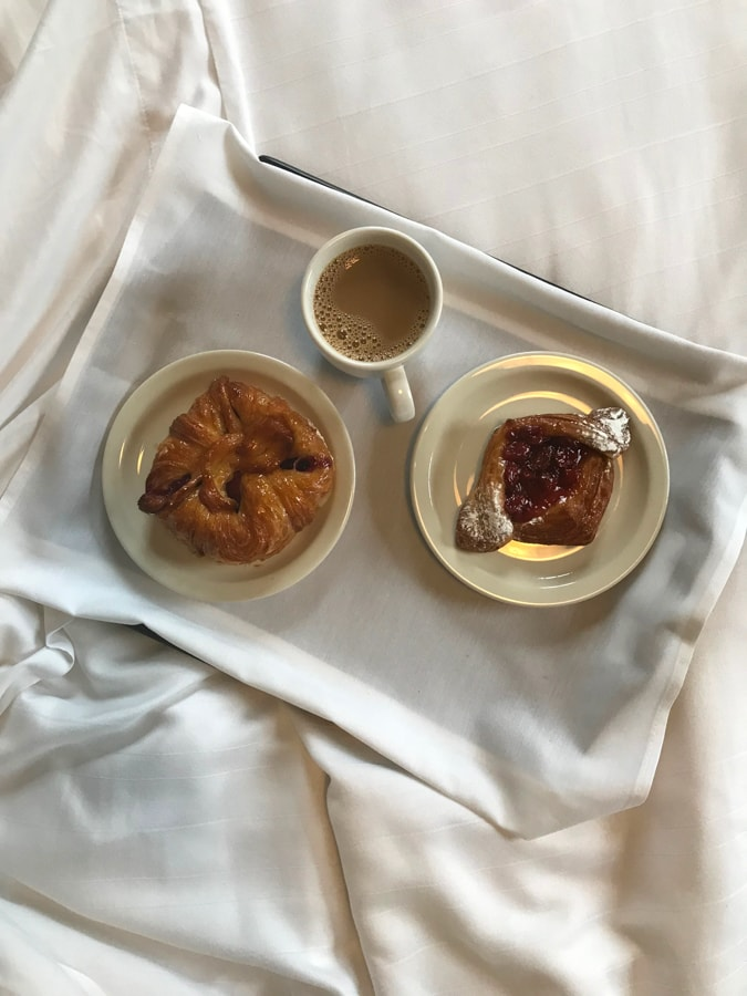 Pastries on a bed with cup of coffee.