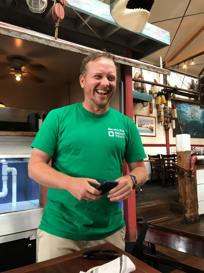 Tour guide in green shirt laughing at restaurant.