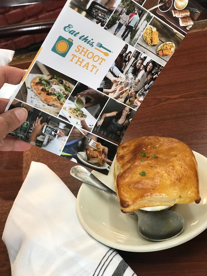 Pot pie on saucer with a spoon and brochure.
