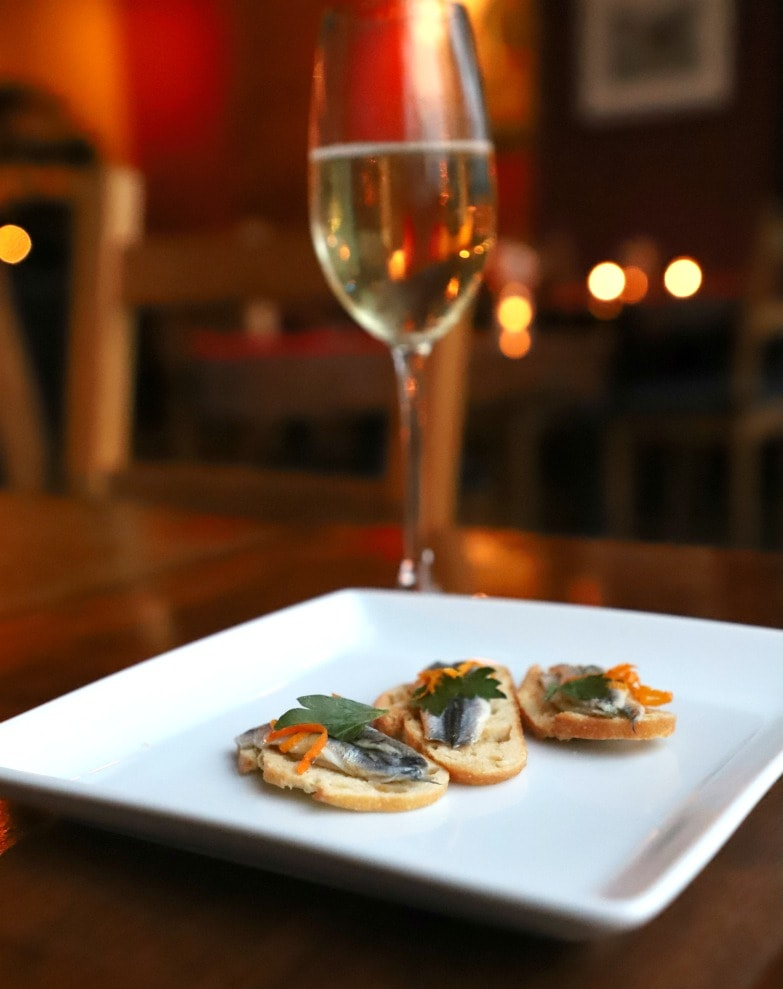 Fish on crostini on white plate with glass of wine in background.
