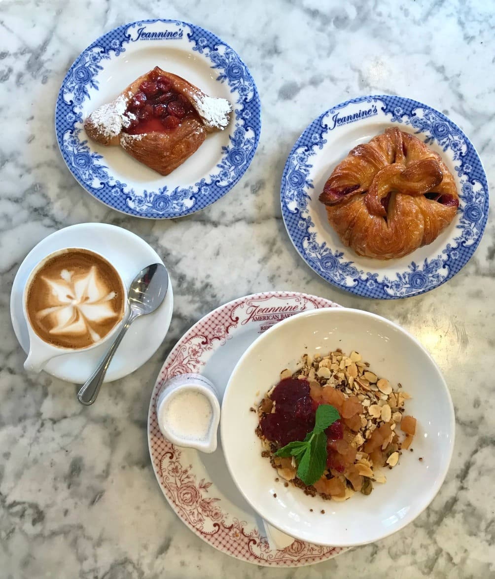 Pastries and granola in bowl with a cappuccino on a marble table.