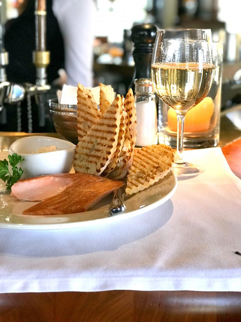 Salmon, bread, and a glass of wine on a white paper placemat.