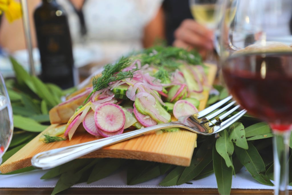 sturgeon, dill, greens, and radishes on a wood board