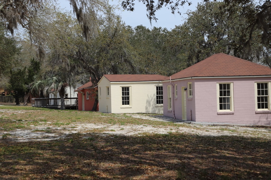 One pink, one white, and one rust colored old historic cottages.