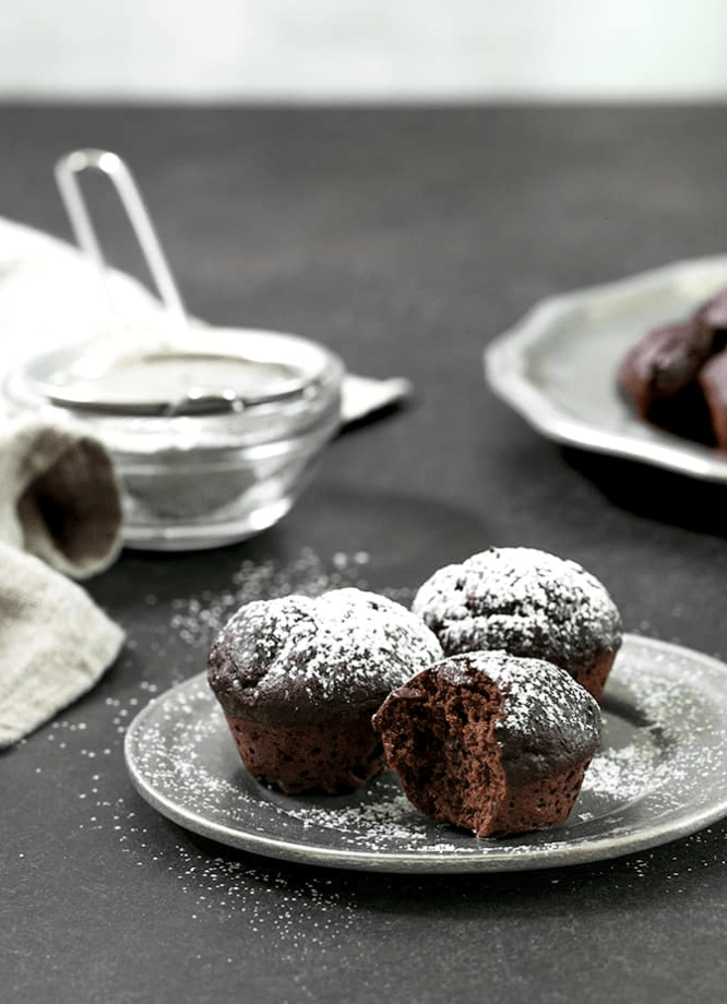brownie muffins on a plate with powdered sugar and sieve