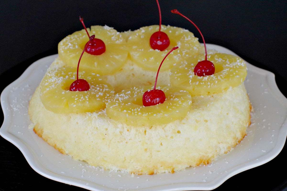 angel food cake with pineapple and cherries on top on white plate