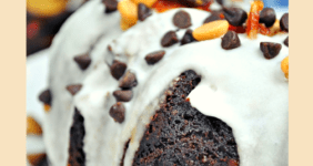 Chocolate rum cake with white icing and chocolate chips and bacon on top.