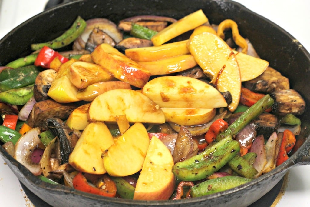 Bratwurst in skillet with apples, peppers, and onions.