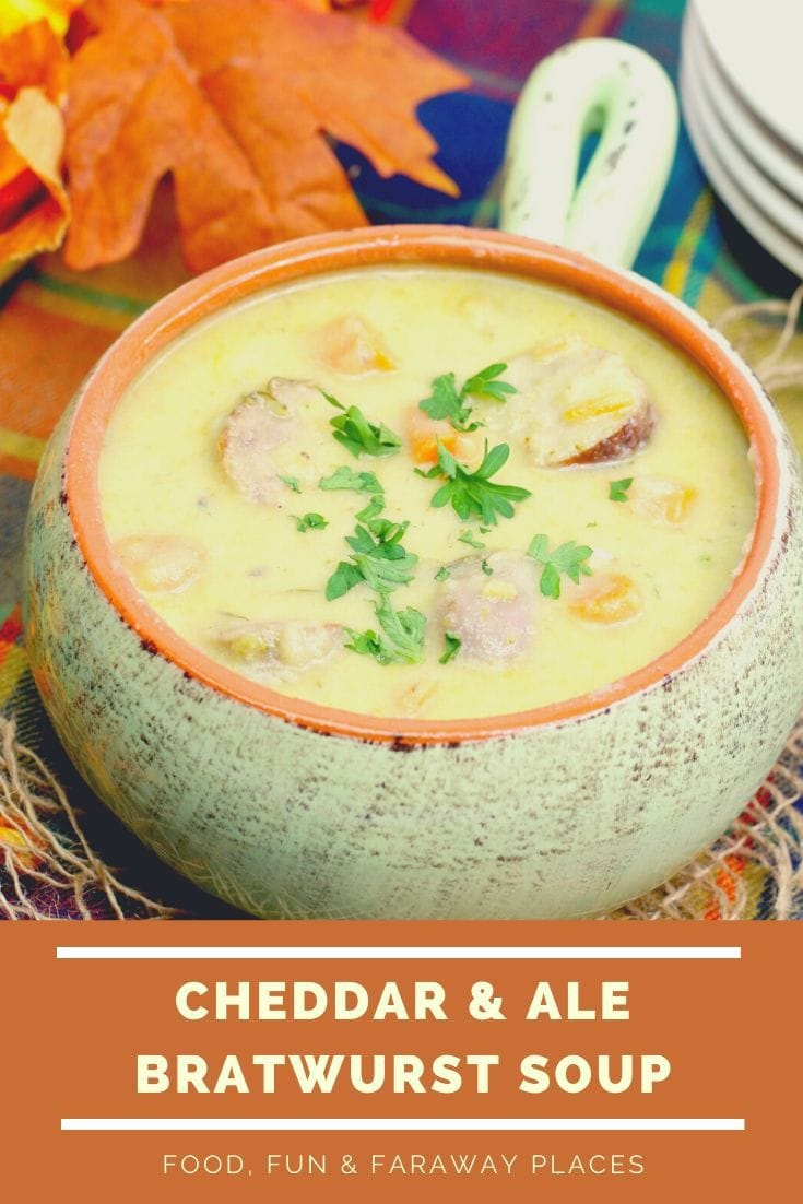 Cheddar ale soup with bratwurst, carrots and parsley in a light green bowl with a handle