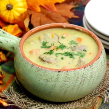 Cheddar cheese soup with bratwurst, carrots and parsley in a light green bowl with a handle