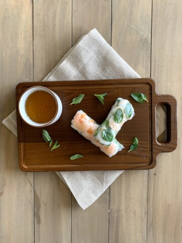 shrimp summer rolls on a cutting board over napkin with sauce on side
