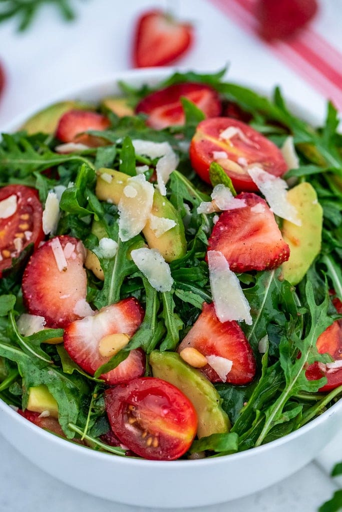 Arugula salad with strawberries  in a white bowl.