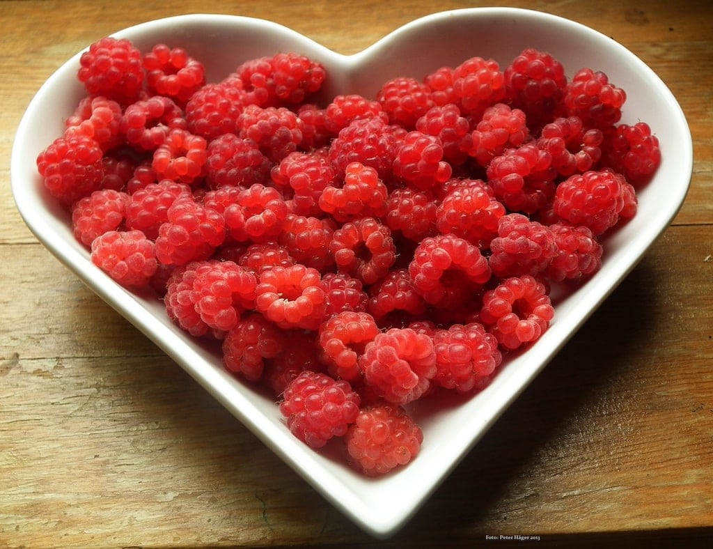 Raspberries in heart shaped bowl.