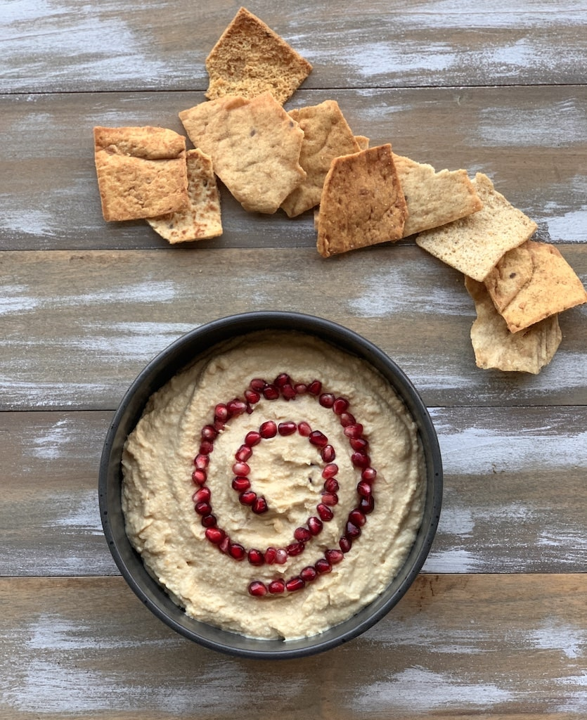 hummus in a black bowl with chips on board