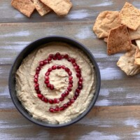 vegan hummus with pomegranate seeds and chips on wood board