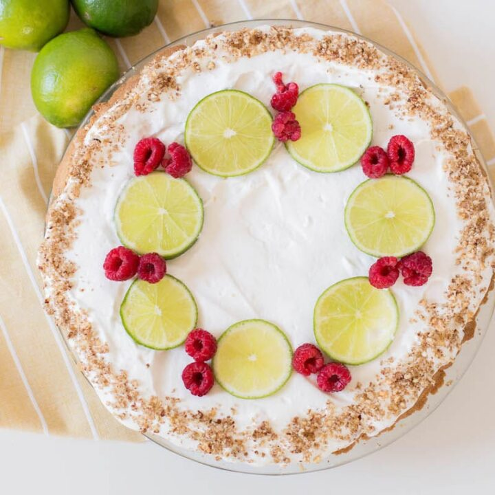 key lime pie with limes and raspberries on yellow napkin