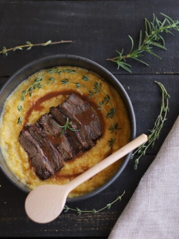 Braised beef over polenta with rosemary, thyme, and juices in a black bowl on a black board.