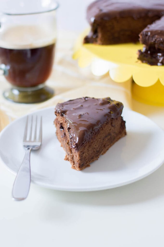 chocolate cake on white plate with coffee in background