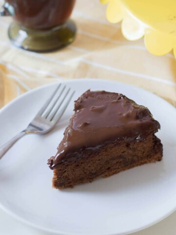 chocolate torte in white plate with yellow tray and coffee in background