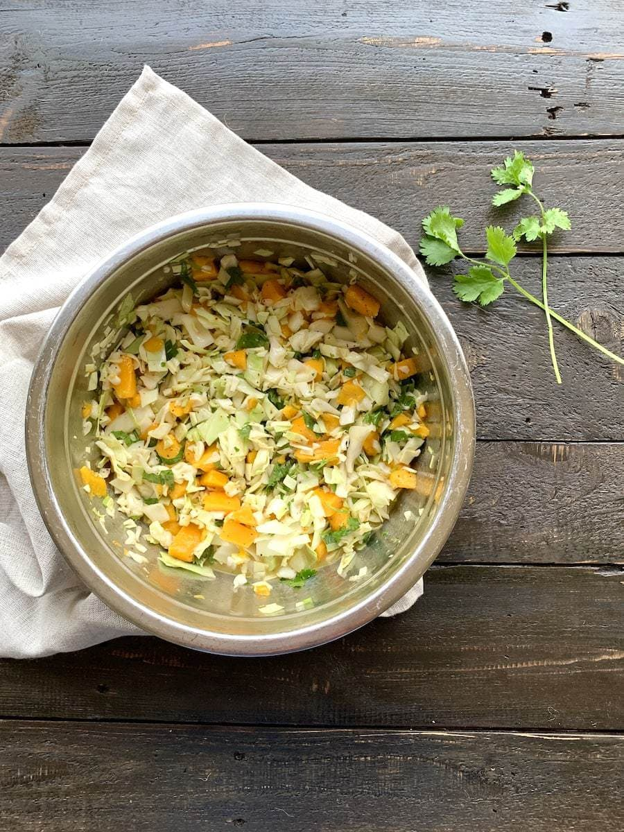 mango, cabbage, cilantro slaw in a silver bowl on a white napkin on a black board
