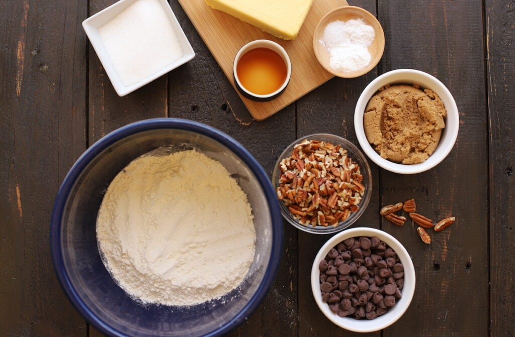 ingredients for chocolate chip pecan cookies on a wood board