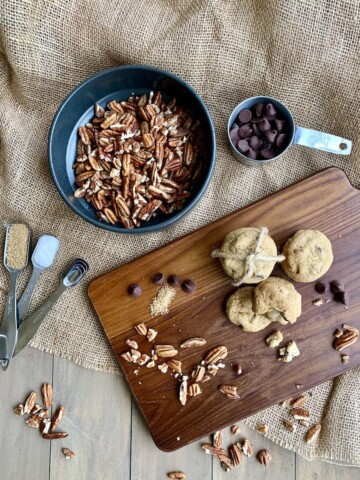 chocolate chip cookies on wood board with pecans, chocolate chips, and spices