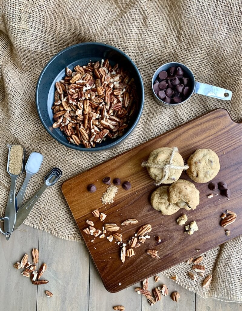 chocolate chip pecan cookies on wood cutting board on burlap with pecans, chocolate chips, and spices