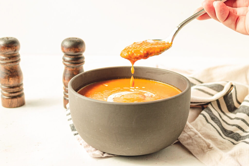 tomato soup with a swirl of coconut  milk on top in a brown bowl on a white table with a white and black cloth and salt and pepper in background