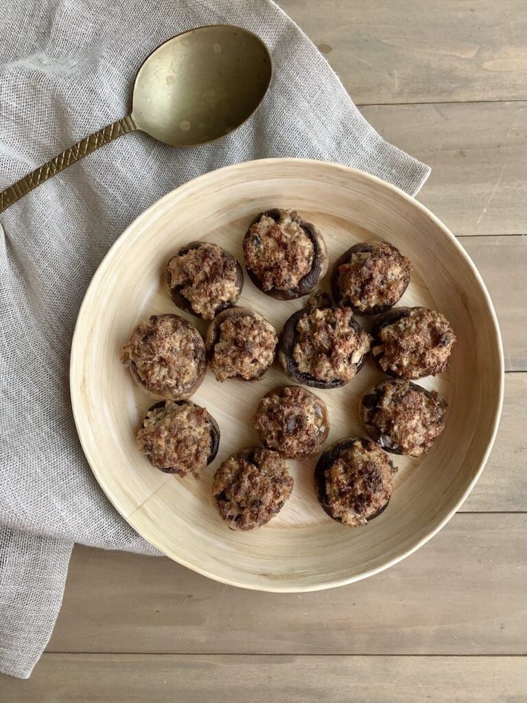classic stuffed mushrooms in a tan dish with a napkin and serving spoon
