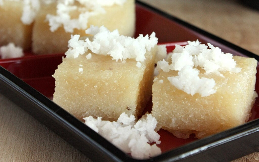 Pieces of cassava cake topped with coconut on a brown tray.