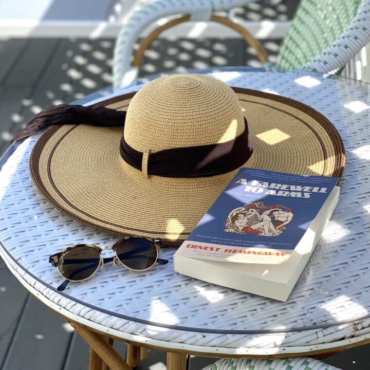 Hat on table with book by pool