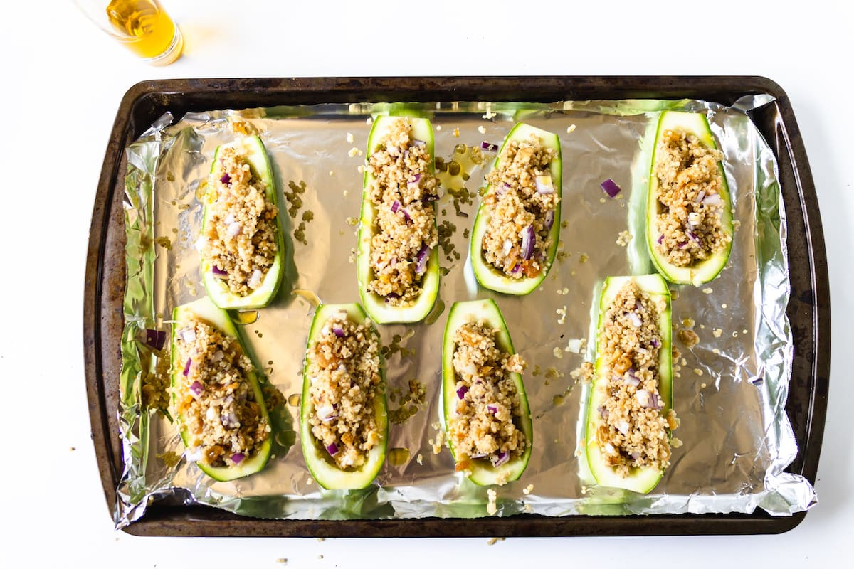 stuffed zucchini on foil on baking sheet