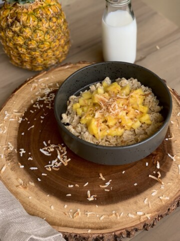 Tropical coconut oatmeal porridge on wood slab.