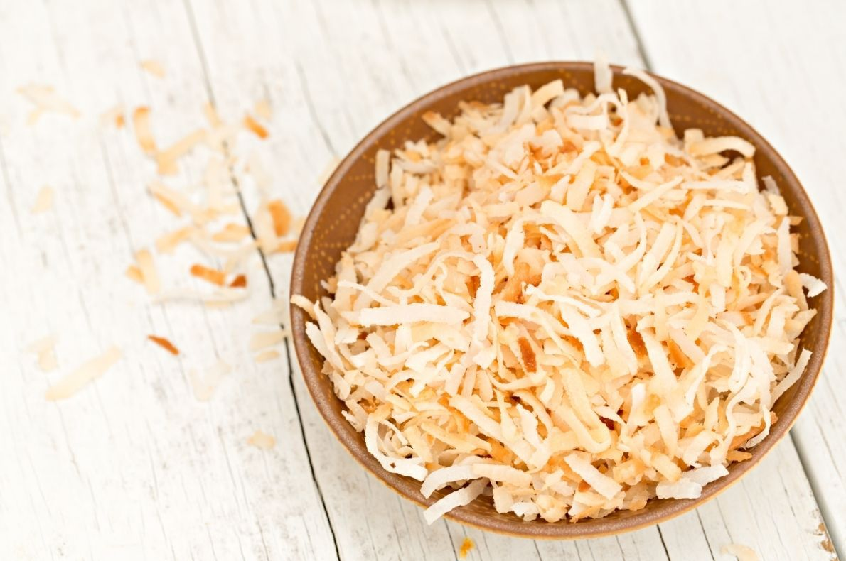 toasted coconut in brown bowl on white table