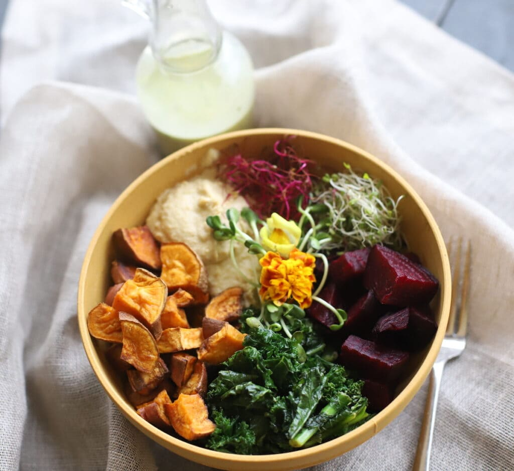 kale and sweet potato vegan power bowl on a cloth with salad dressing on the side