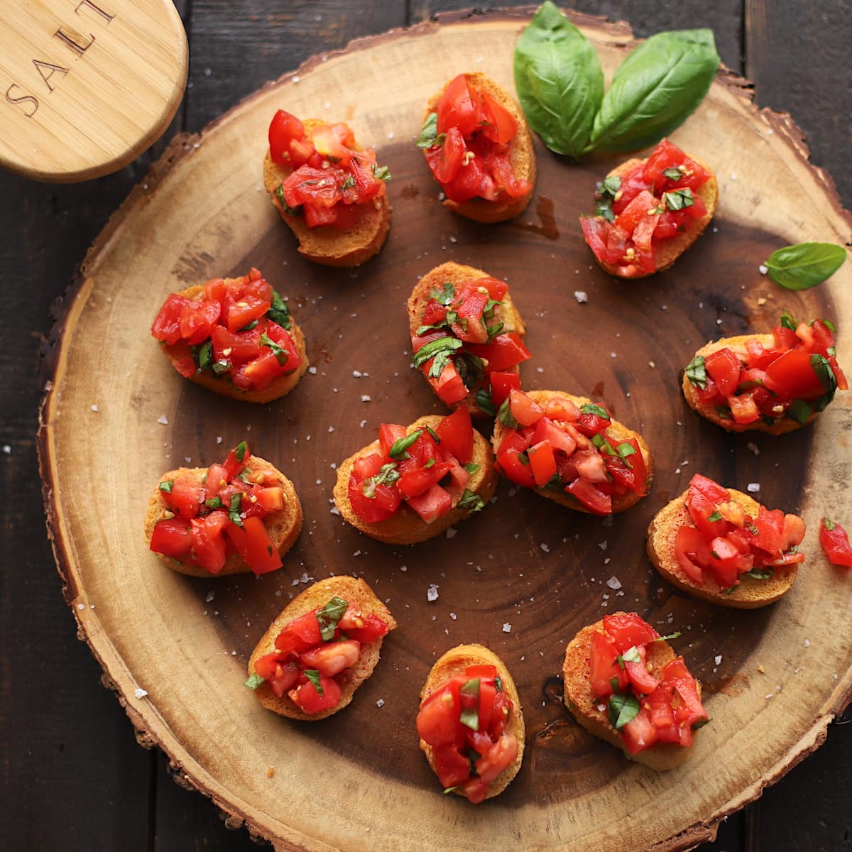 Tomatoes and basil on bread on a wood slab.