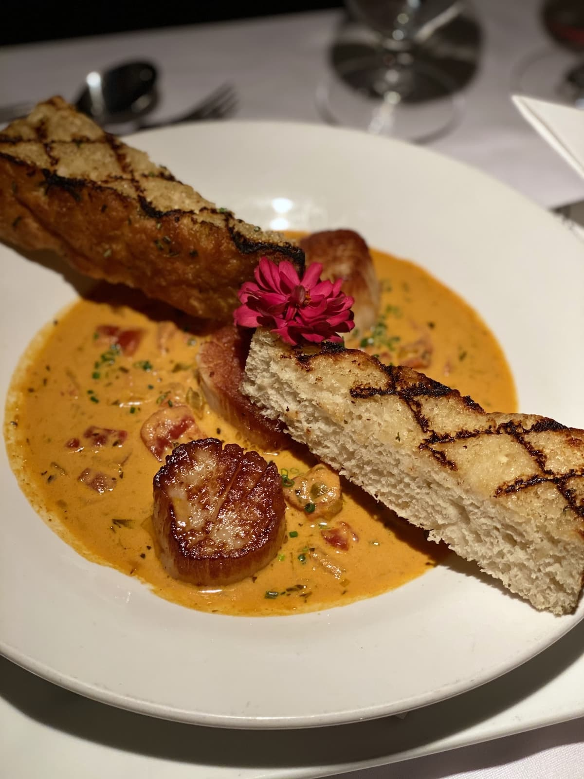 Scallops in a tomato broth with slices of grilled bread
