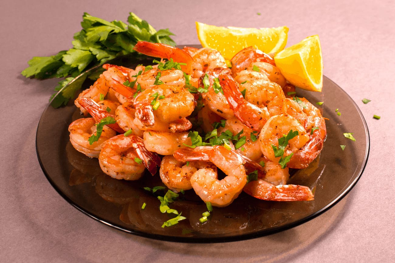 Shrimp on a plate with lemon and parsley.
