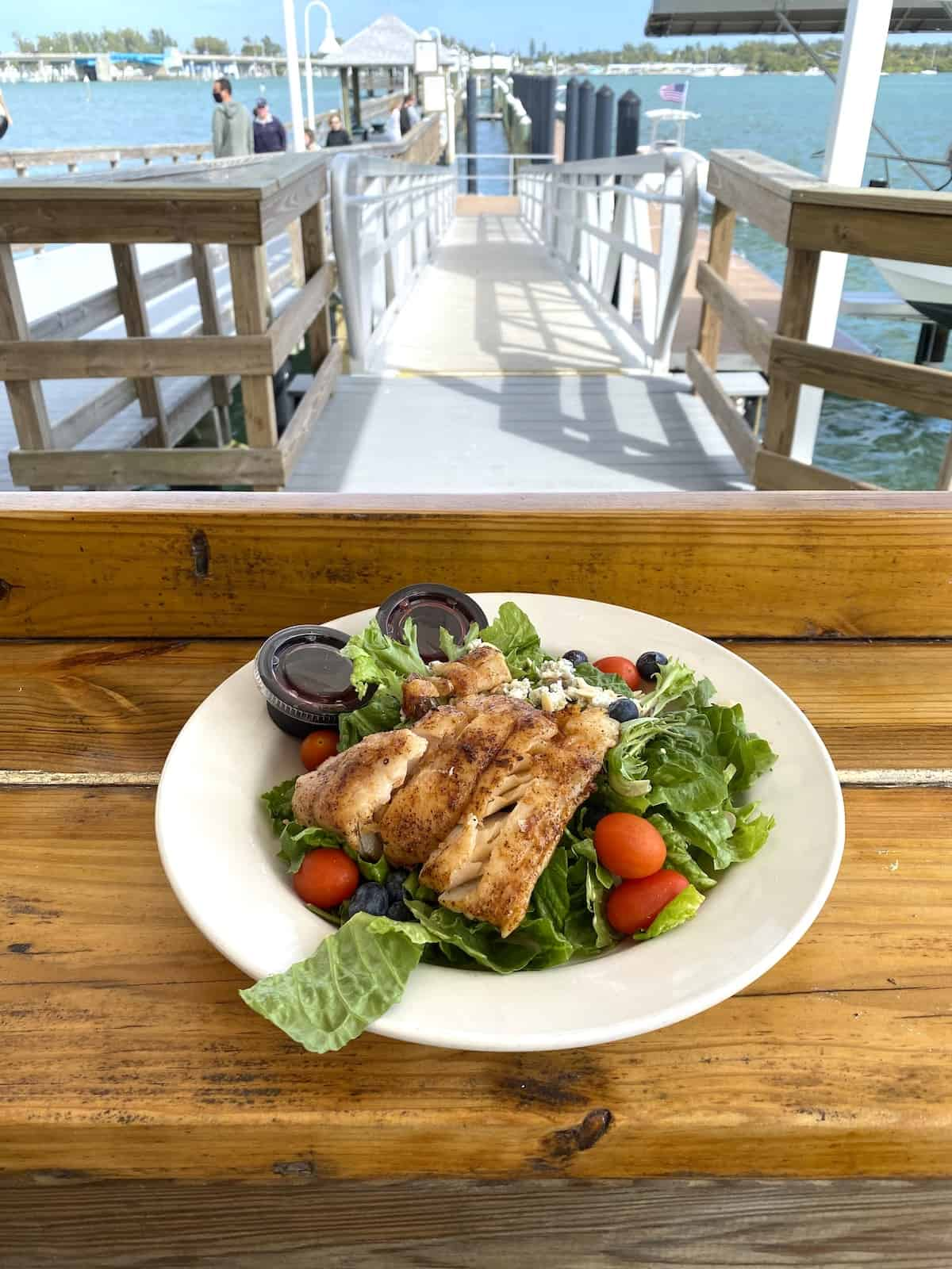 Grouper on a salad in a white bowl on a wood bar.